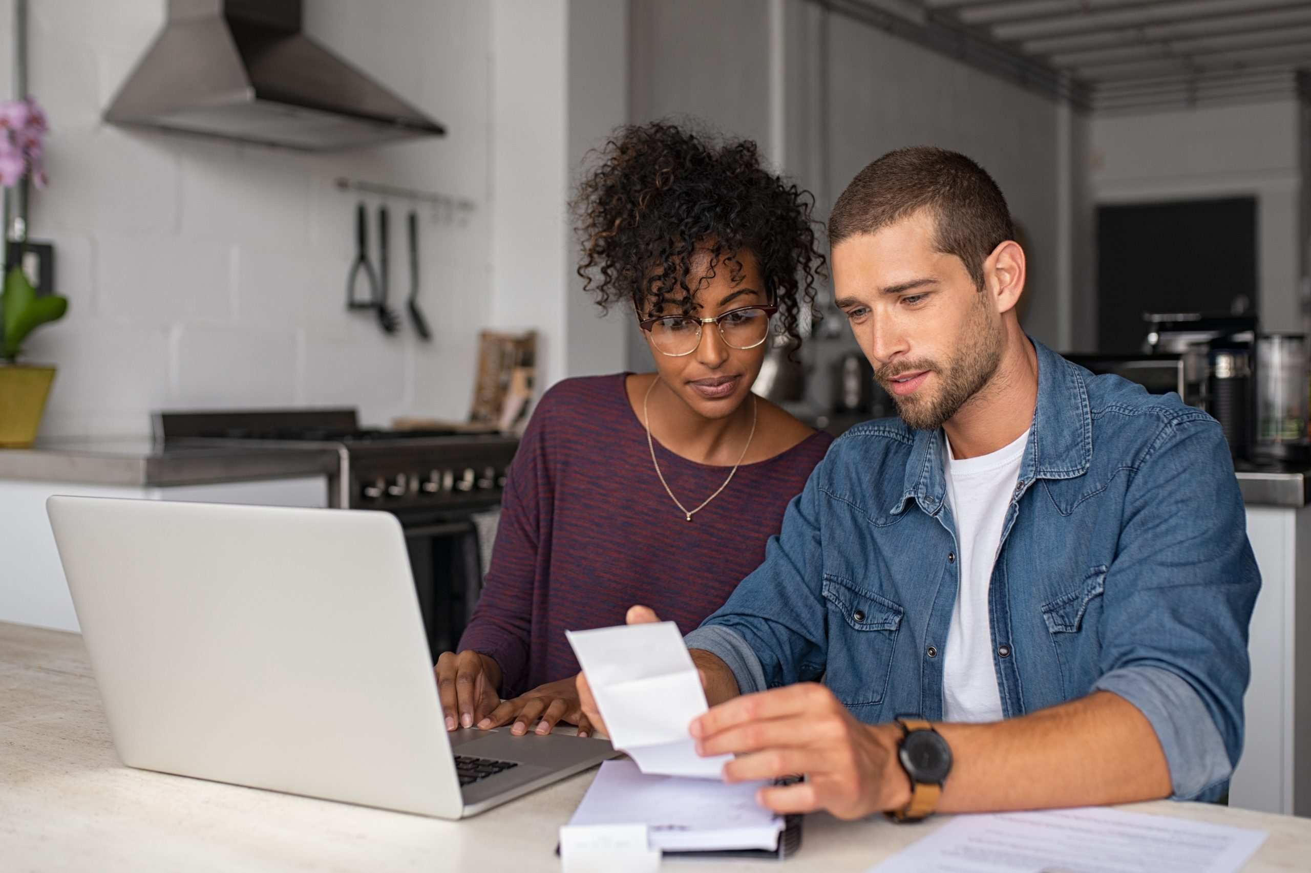 a young couple sitting at their kitchen table looking over personal finances